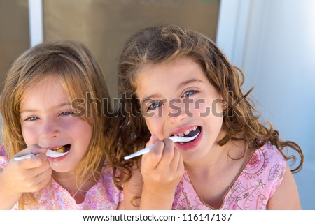 Blue eyes kids sister girl eating breakfast with spoon - stock photo