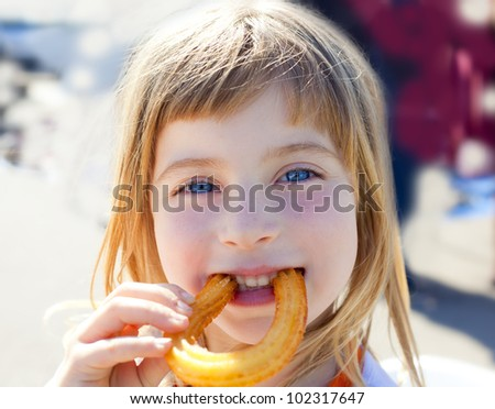 Blue eyes little girl eating churros fried crullers smiling - stock photo