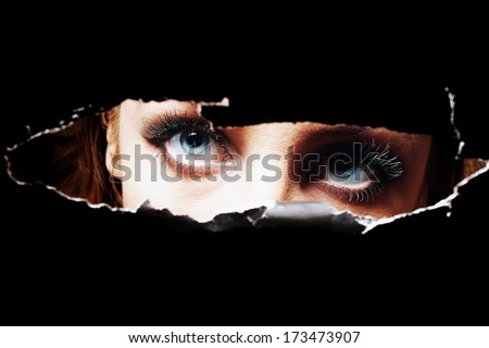 Blue eyes of young woman peeping through a hole closeup - stock photo