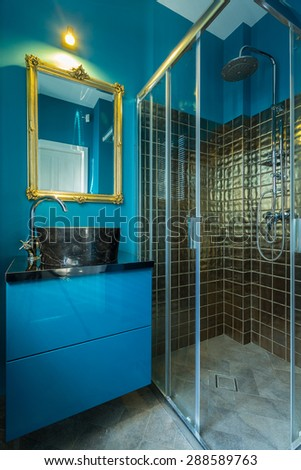 Blue fashionable bathroom with golden tiles in shower - stock photo