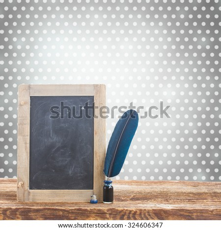 Blue  feather pen on  wooden table and  empty blackboard with copy space - stock photo