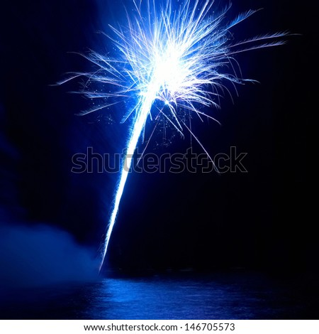 Blue fireworks on the black sky background. Holiday celebratio - stock photo