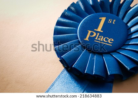 Blue first place winner rosette or badge from pleated ribbon with central text to be awarded to the winner of a competition on a graduated beige background with copyspace - stock photo