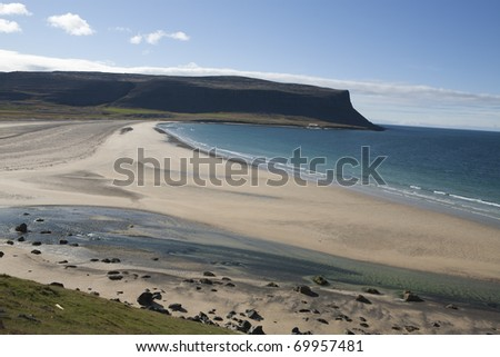 Blue fjord green mountains ocean beach in Iceland - stock photo