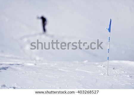 Blue flag blown by the wind on a mountain in winter and skier in background - stock photo
