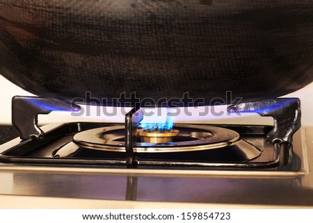 Blue Flame of a Gas Cooker heating a Wok - stock photo