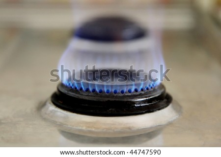 Blue flame of an old gas stove. Side view - stock photo