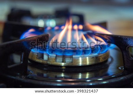Blue flames on gas stove burner. - stock photo