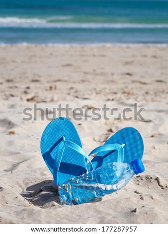 Blue flip flops and bottle of water on sand beach - stock photo
