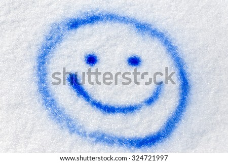 blue funny smiley sprayed in the snow - stock photo
