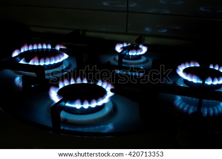 Blue Gas Stove Flames of multiple hobs, dark background - stock photo
