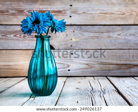 blue gerbera flower in a vase on wooden background - stock photo