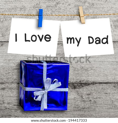 blue gift box on wooden wall with a blank paper hanged and I love my dad message, father's day concept. - stock photo