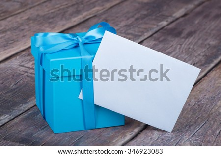 Blue gift box with blank greeting card envelope  - stock photo