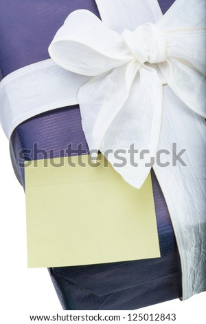 Blue gift box with white ribbon and yellow note on white background - stock photo