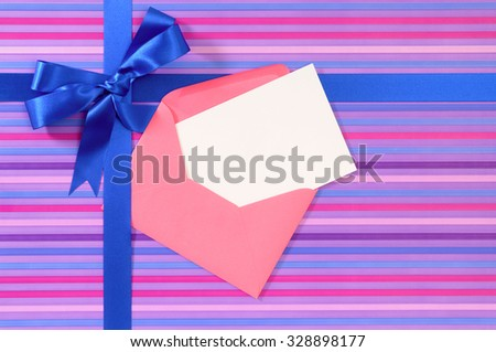 Blue gift ribbon bow on candy stripe wrapping paper, blank Christmas or birthday card and envelope, copy space - stock photo