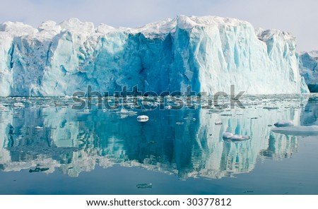 Blue glacier reflecting in the waters of fjord - stock photo