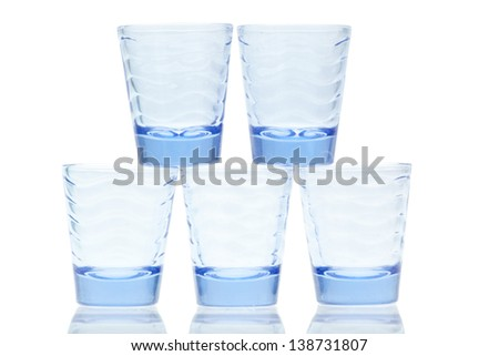 Blue glass stacked shot glasses on a white background - stock photo