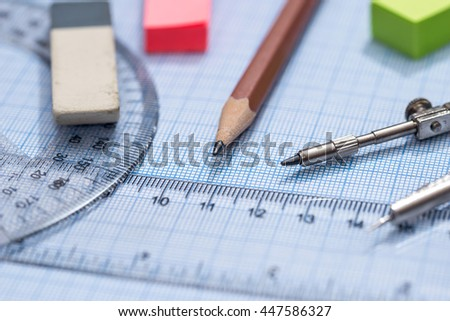 blue graph paper with drawing tools - stock photo