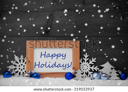 Blue Gray Christmas Decoration On Snow. Christmas Tree Balls, Snowflakes, Christmas Tree. Picture Frame With English Text Happy Holidays. Rustic, Vintage Brown Wooden Background. Black And White Image - stock photo