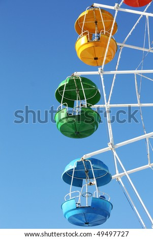 Blue, green and yellow ferris wheel carriages - stock photo