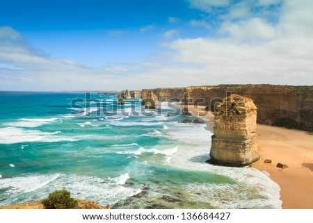 Blue green ocean and beach with sandbanks cliffs and waves  with wide view of The twelve apostles and cliffs in the shadow of the late afternoon sun in Victoria, Australia against a blue cloudy sky - stock photo