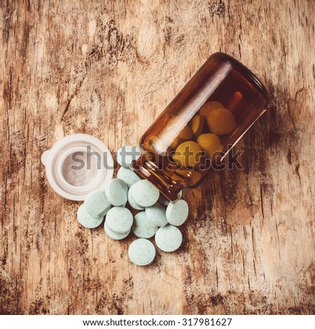 Blue-green pills spilled from open cans of dark glass lying on an old table. - stock photo