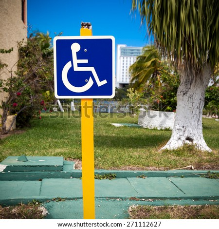 Blue handicapped sign with wheelchair, outdoors  - stock photo