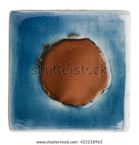 Blue handmade glazed ceramic tile with brown dot in middle isolated on white - stock photo