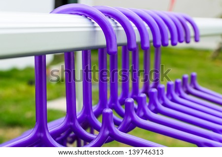 Blue hangers hanging on the bar - stock photo