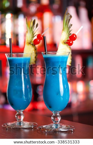 Blue Hawaiian cocktails shot in dim red light in a club - stock photo