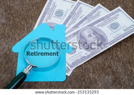 Blue home sign with magnifying glass and money: Retirement - stock photo