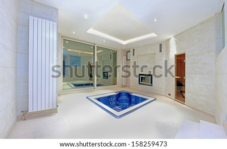 Blue hottub in the middle of large interior - stock photo