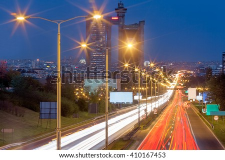 Blue hour shot of speed drive on freeway at the entrance to Belgrade, Serbia with a view to the West Towers - west gate in the background. Light trails at rush hour on motorway in long exposure shot. - stock photo