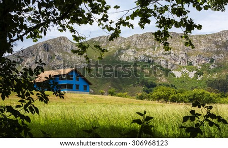 Blue house in the mountains - stock photo