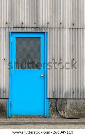 Blue industrial door and gray corrugated exterior walls.  - stock photo