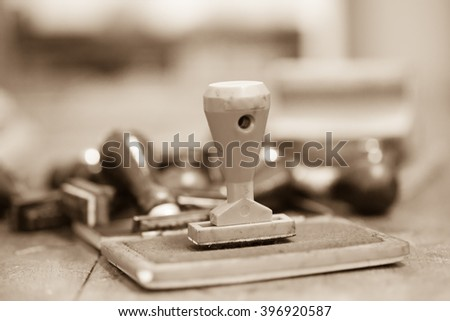 Blue ink box and rubber stamp on wooden table in sepia tone - stock photo