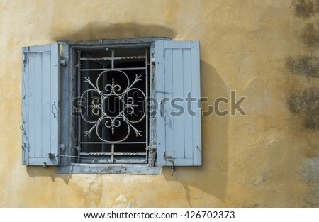 Blue iron window on a worn stucco wall. Antique european style. - stock photo