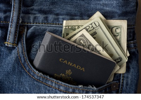 Blue jean pocket with Canadian Passport and USA currency - stock photo