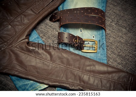 Blue jeans, a leather belt with a buckle and leather jacket. dark tone - stock photo