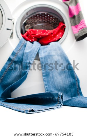 Blue jeans and red shirt hanging out from the door of the washing machine. Space for copy on the floor. Focus is on the lower part of the jeans. Isolated on white background. - stock photo