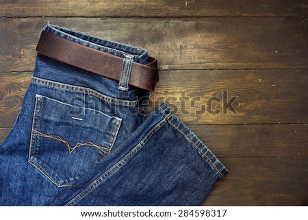 Blue jeans with belt on wooden background - stock photo