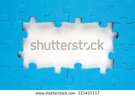 Blue jigsaw puzzle pieces arranged as a border around a wooden surface  with space for your text - stock photo