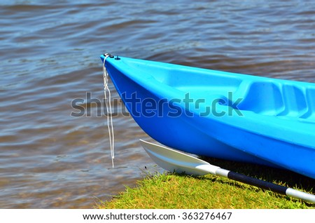 Blue kayak on river bank. Watersport concept. - stock photo
