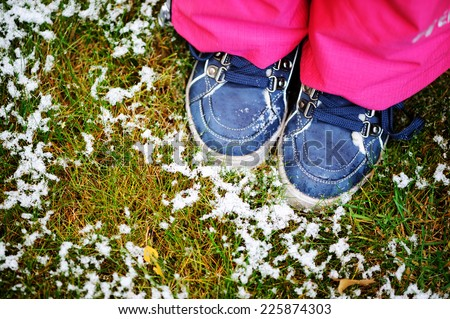 Blue kid girl boots on the grass with first snow on it - stock photo