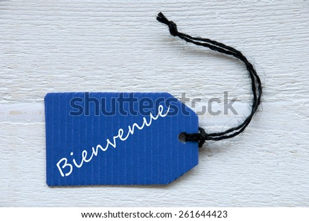Blue Label Or Tag With Black Ribbon On White Wooden Background With French Text Bienvenue Which Means Welcome Vintage Retro Or Rustic Style - stock photo