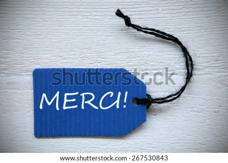 Blue Label Or Tag With Black Ribbon On White Wooden Background With French Text Merci Which Means Thank You Vintage Retro Or Rustic Style - stock photo