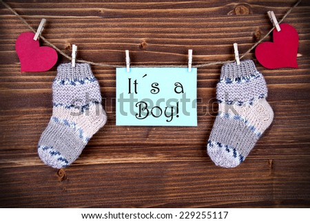 Blue Label with the Words It's a Boy and Baby Socks and red Hearts on a Line on wooden Background - stock photo