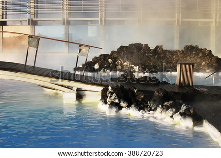 Blue lagoon with a pedestrian bridge in the lagoon spa showing the accumulation of silica minerals in the points of contact of water with the volcanic rock - stock photo