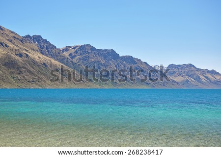 Blue lake and mountains in lake Wakatipu, New Zealand - stock photo